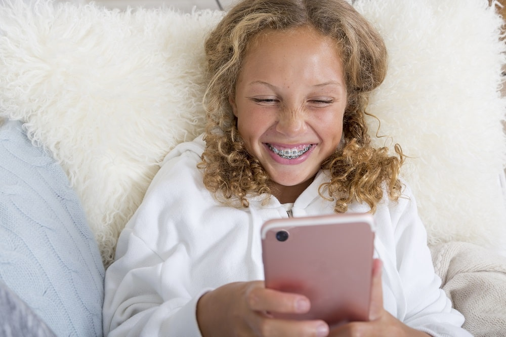 Girl with braces using phone