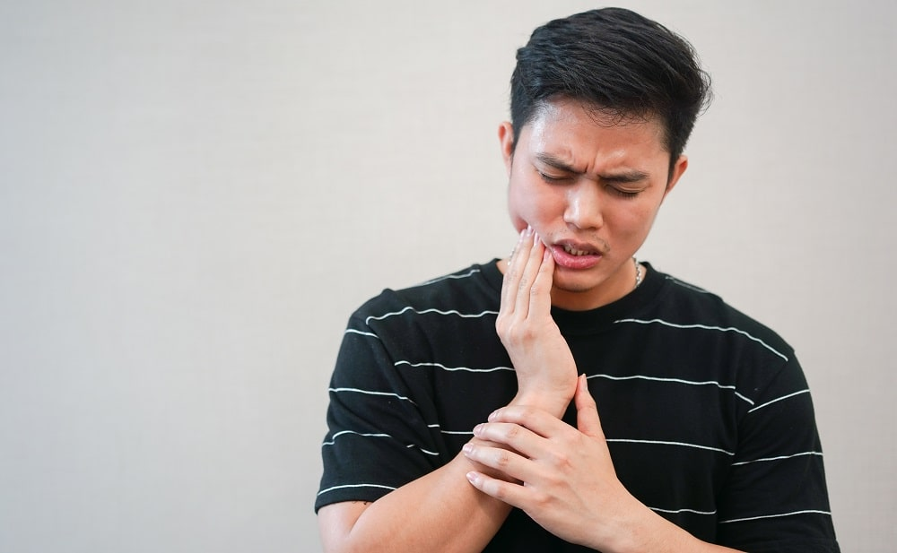 man touching jaw in pain