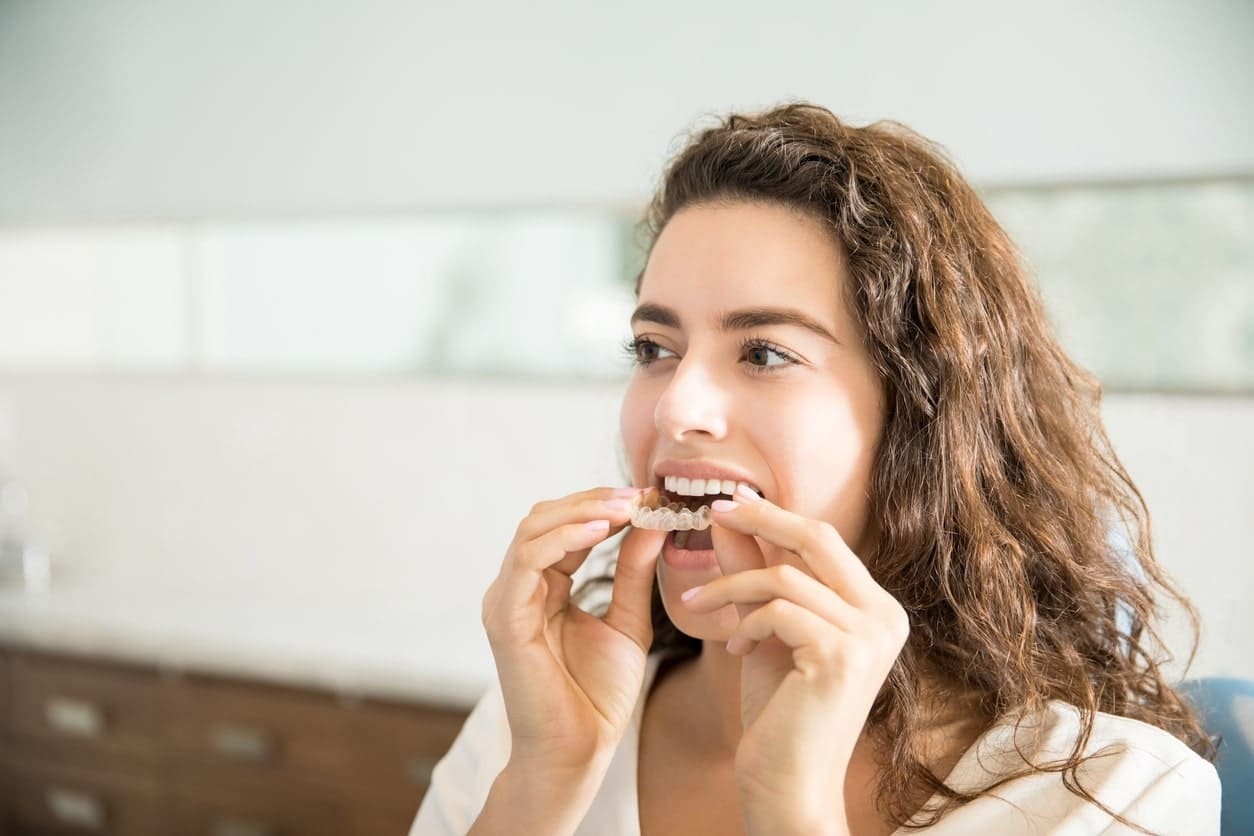 woman inserting her invisalign braces