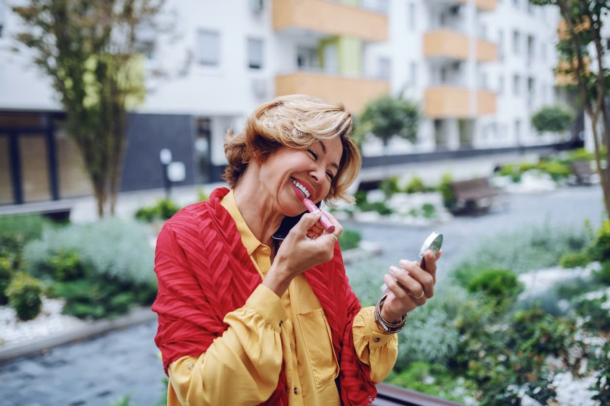 woman smiling putting lipstick on outside