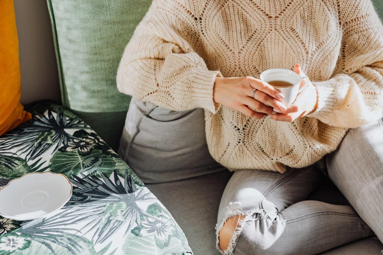 woman on couch enjoying tea